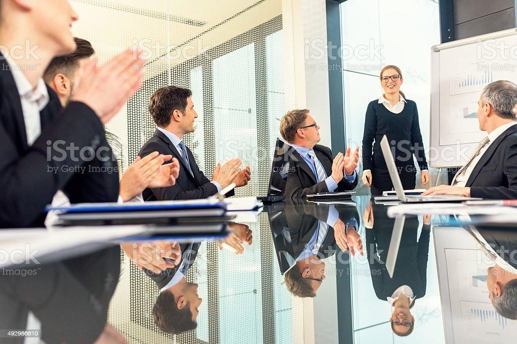 Homens de negócios aplaudindo a apresentação de uma jovem Empresária - foto de acervo
