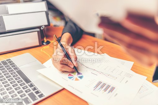 1024730528 istock photo Businessmen are analyzed data from report using smartphone and laptop computer. 1005846546