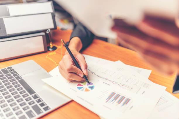 affärsmän är analyserade data från rapporten med hjälp av smartphone och laptop dator. - projektledning bildbanksfoton och bilder