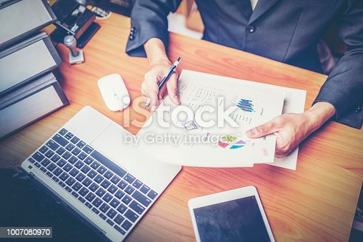 1024730528 istock photo Businessmen are analyzed data from report using smartphone and laptop computer. 1007080970
