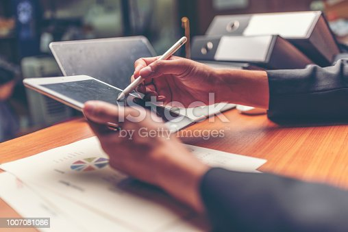 1024730528 istock photo Businessmen are analyzed data from report using smartphone and laptop computer. 1007081086