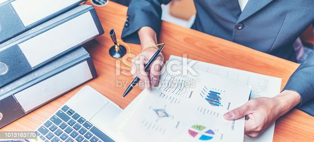 1024730528 istock photo Businessmen are analyzed data from report using smartphone and laptop computer. 1013163770