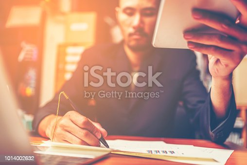 1024730528 istock photo Businessmen are analyzed data from report using smartphone and laptop computer. 1014002632