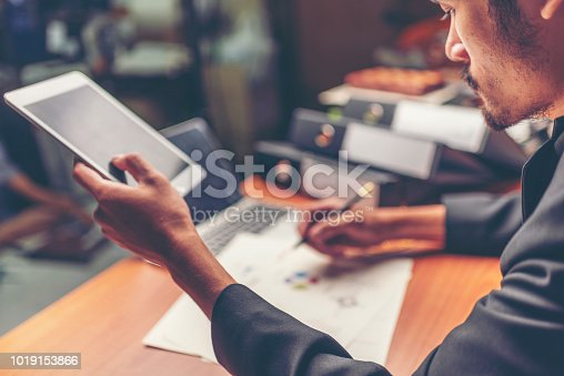 1024730528 istock photo Businessmen are analyzed data from report using smartphone and laptop computer. 1019153866