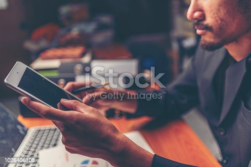 1024730528 istock photo Businessmen are analyzed data from report using smartphone and laptop computer. 1026406108