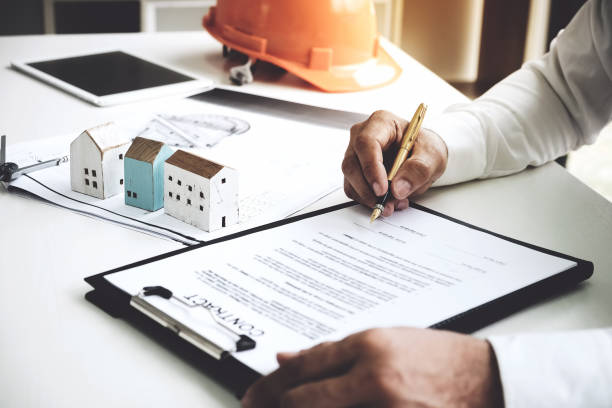 businessmen are checking the contract to use the right pen. signed building approval with blueprint and house model on the table. - consumerism stock pictures, royalty-free photos & images