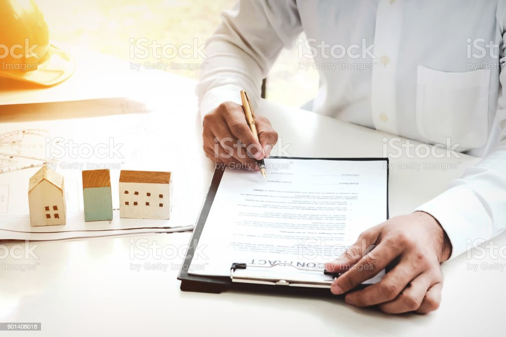 Businessmen are checking the contract to use the right pen. Signed building approval with blueprint, house model and helmet on the table. stock photo