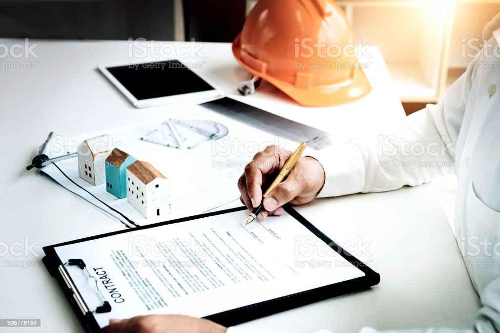 Businessmen are checking the contract to use the right pen. Signed building approval with blueprint and house model on the table. stock photo
