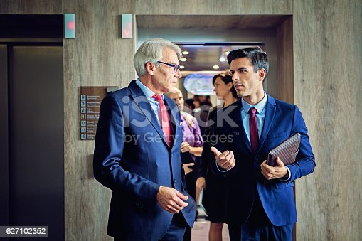 Businessmen are exiting from the elevator in the company building discussing between them.