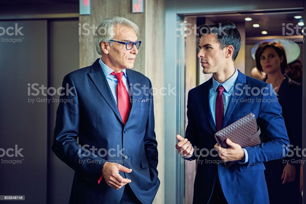 Businessmen are exiting from the elevator in the company building discussing between them stock photo
