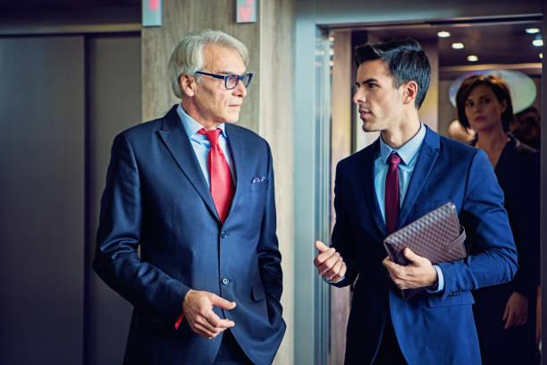 Hommes d'affaires sont sortant de l'ascenseur dans l'entreprise de construction à discuter entre eux - Photo