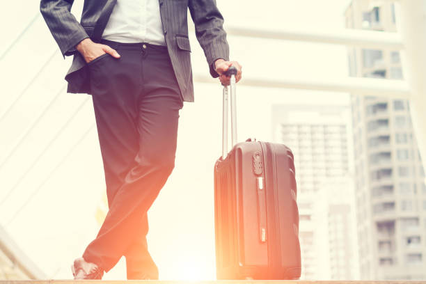 Businessmen are standing in the morning sunrise, business man going to the airport with luggage, concept of business transportation and traveling holiday leave weekend. stock photo