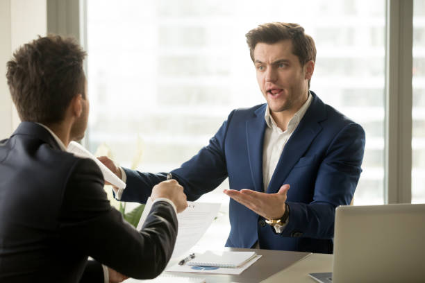 Businessmen arguing at workplace, deal failure, breaking contract, unacceptable terms stock photo