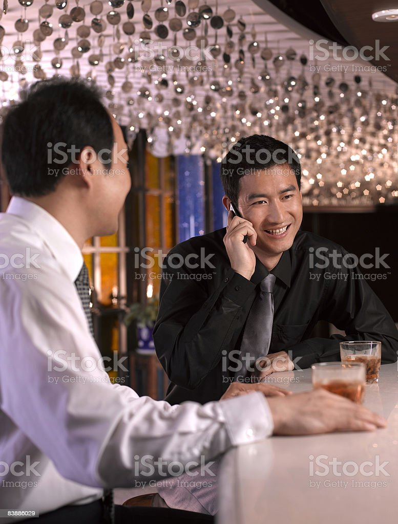 Businessmen at bar, one on cell phone. royaltyfri bildbanksbilder