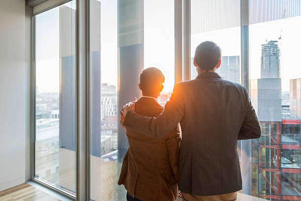 Businessmen at office window in sunlight, arm around stock photo