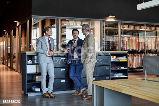 Full length of businessmen communicating in textile factory. Male colleagues are standing by cabinet. They are wearing suits in office.