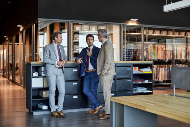 Businessmen communicating in textile factory stock photo