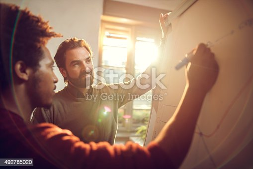 istock Businessmen cooperating while drawing a business chart at office 492785020