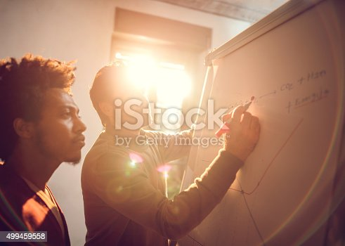 497812268 istock photo Businessmen cooperating while drawing a business chart at office. 499459558