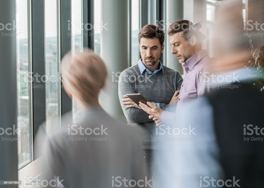 Businessmen cooperating while working on digital tablet in a hallway. stock photo