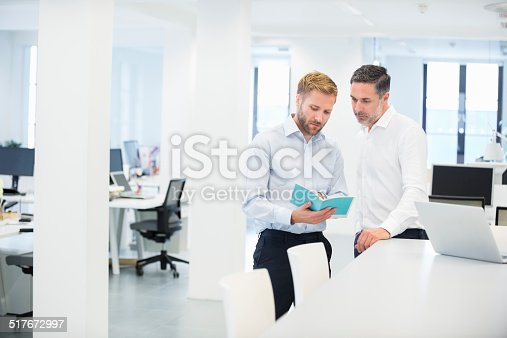 istock Businessmen Discussing Booklet In Office 517672997
