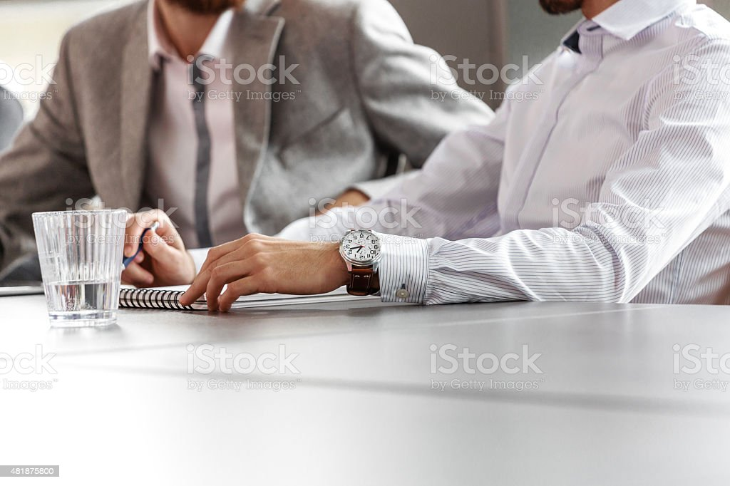 Businessmen discussing in an office, close up of hands Two businessmen sitting at the conference table discussing and writting notes. Close up of hands, unrecognizable people. Ring binder and glass of water on the table. 2015 Stock Photo