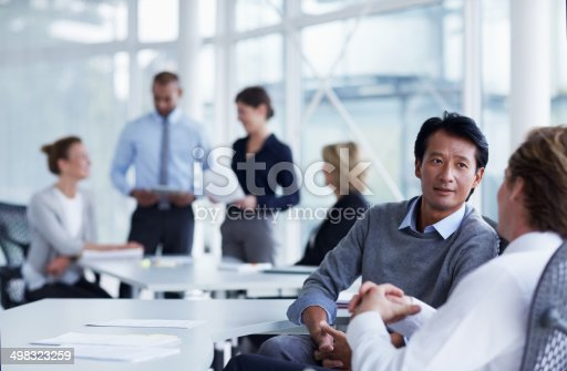 Businessman discussing with male colleague in office