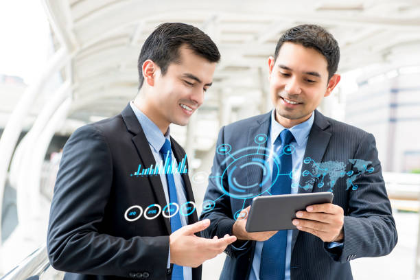 Businessmen discussing investment project on tablet computer stock photo
