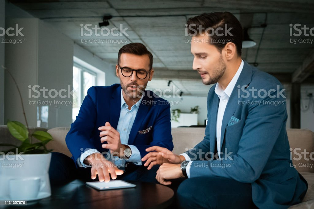 Businessmen discussing over digital tablet Confident businessmen discussing over digital tablet. Male professionals are planning strategy during meeting. They are working at creative office. 30-39 Years Stock Photo