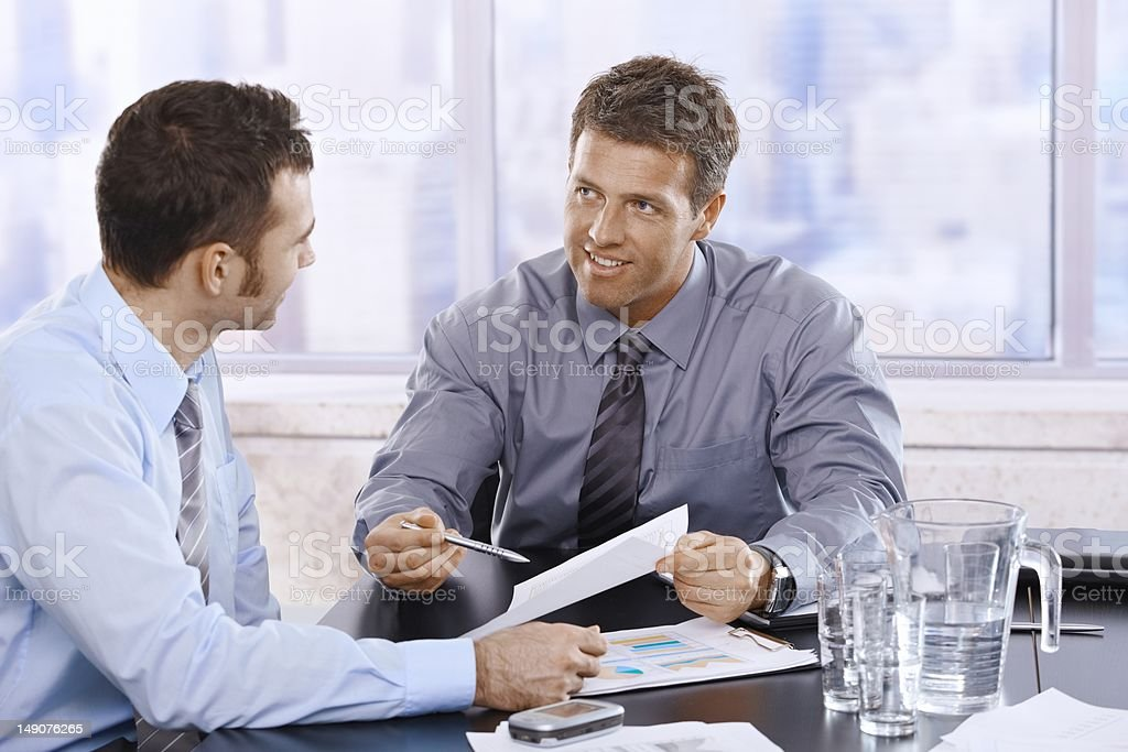 Businessmen discussing report royalty-free stock photo