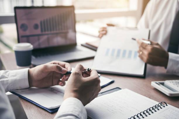 Geschäftsleute erklären mit Kollegen und Unternehmern quartalsweise Ergebnisse und diskutieren im Büro über die künftige Finanzplanung. – Foto