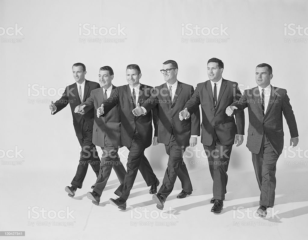 Businessmen extending hand to shake, smiling stock photo