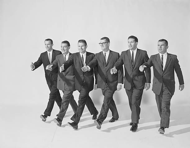 businessmen extending hand to shake, smiling - archival stock photos and pictures