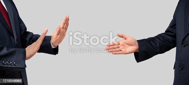 Businessmen facing each other and recommending a handshake and businessmen refusing. Social distance