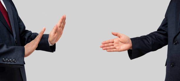 Businessmen facing each other and recommending a handshake and businessmen refusing. Social distance. stock photo