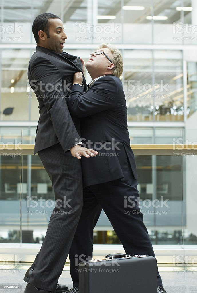 Businessmen fighting in office royalty-free stock photo