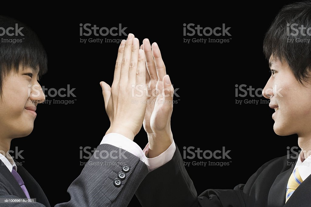 Businessmen giving high-five to each other, smiling foto de stock libre de derechos