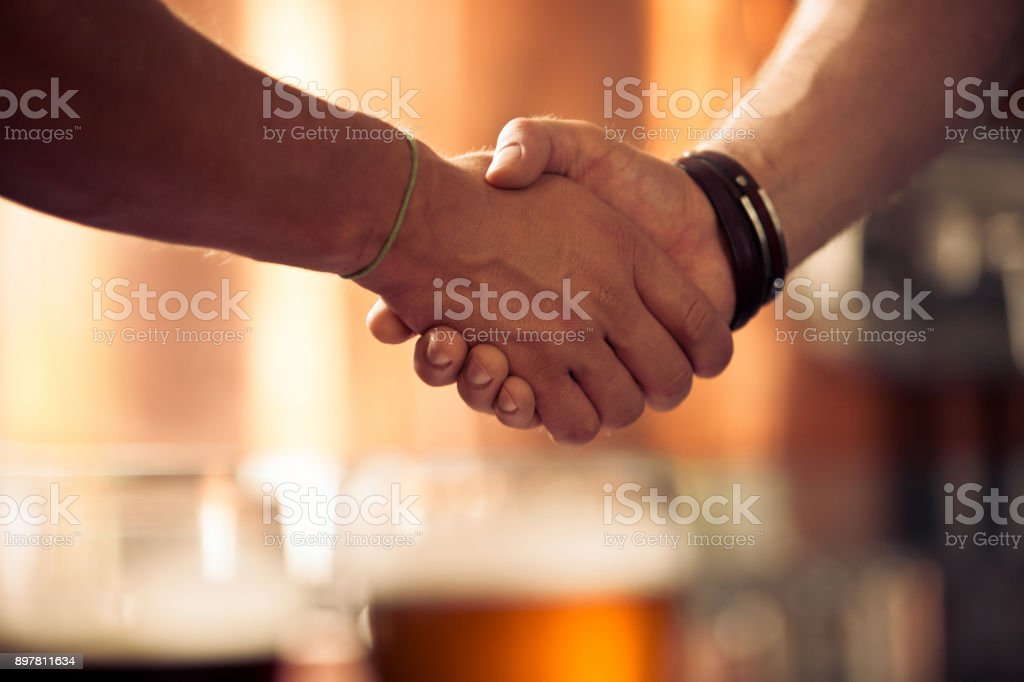 Businessmen hand shake at micro brewery Close up of two businessmen shaking hands at micro brewery. Focus on shaking hands with beer glasses in background. Adult Stock Photo