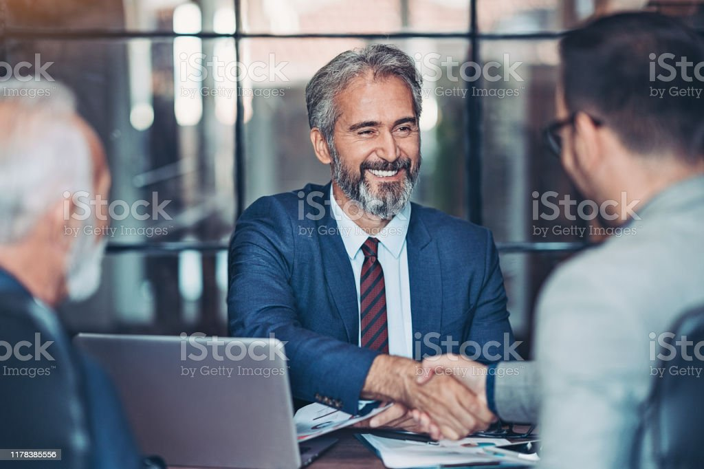 Businessmen handshake in the office Mature businessman shake hands with a younger colleague Active Seniors Stock Photo