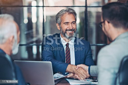 Mature businessman shake hands with a younger colleague