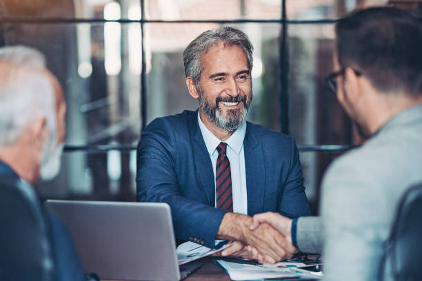 Businessmen handshake in the office Mature businessman shake hands with a younger colleague alliance stock pictures, royalty-free photos & images