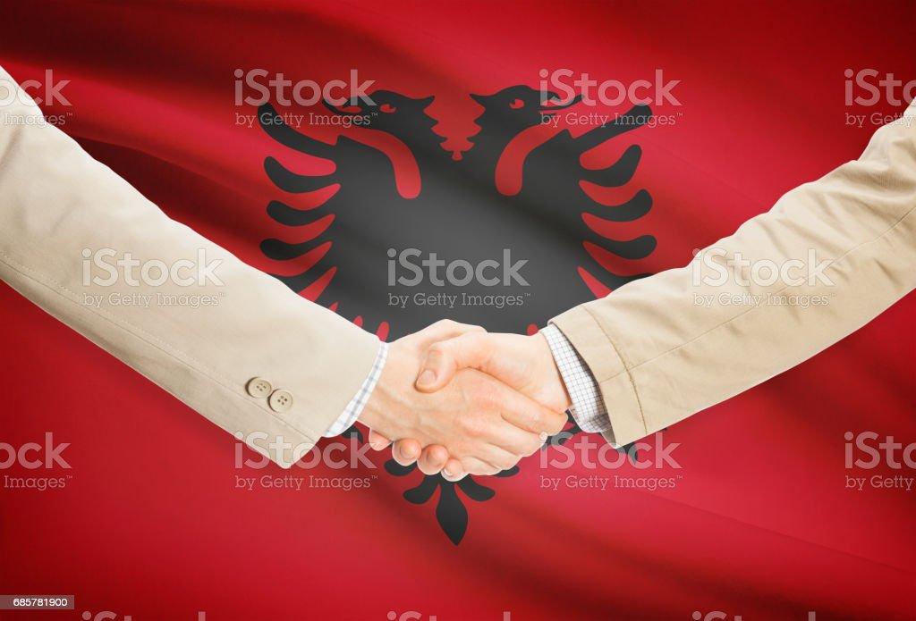 Businessmen handshake with flag on background - Albania royalty-free stock photo