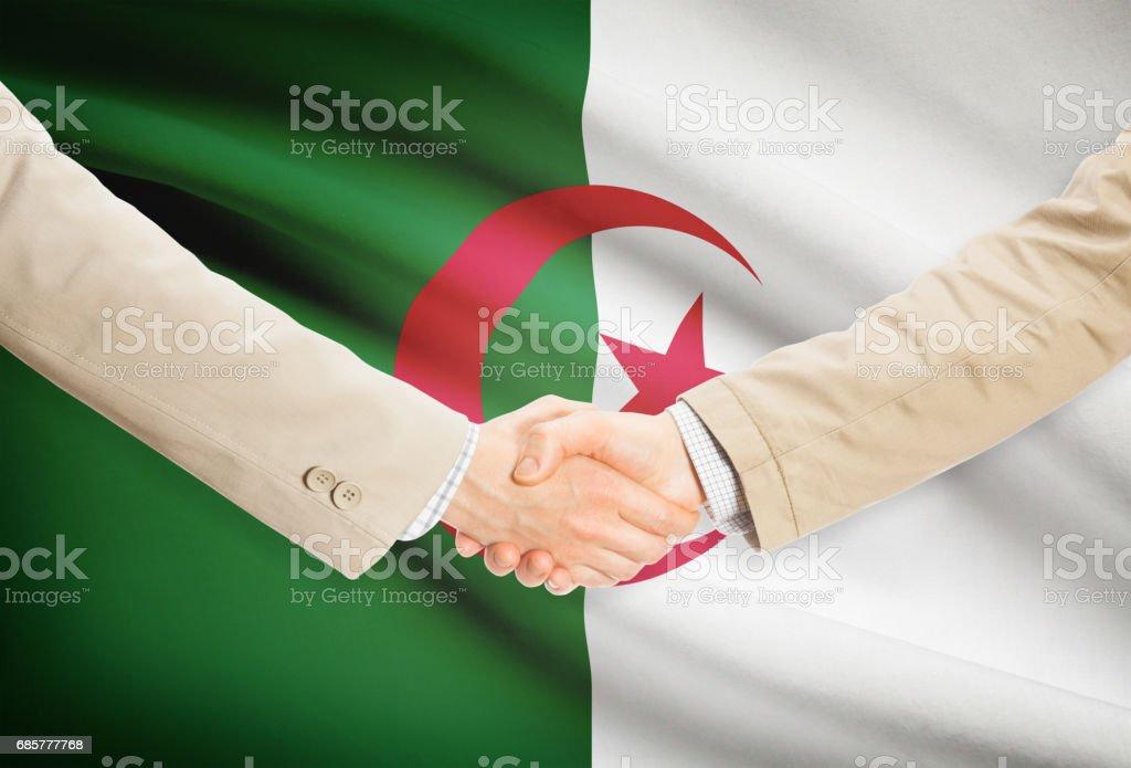 Businessmen handshake with flag on background - Algeria royalty-free stock photo