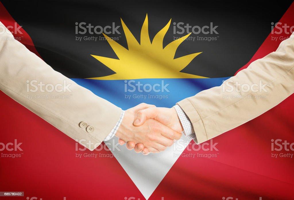 Businessmen handshake with flag on background - Antigua and Barbuda stock photo