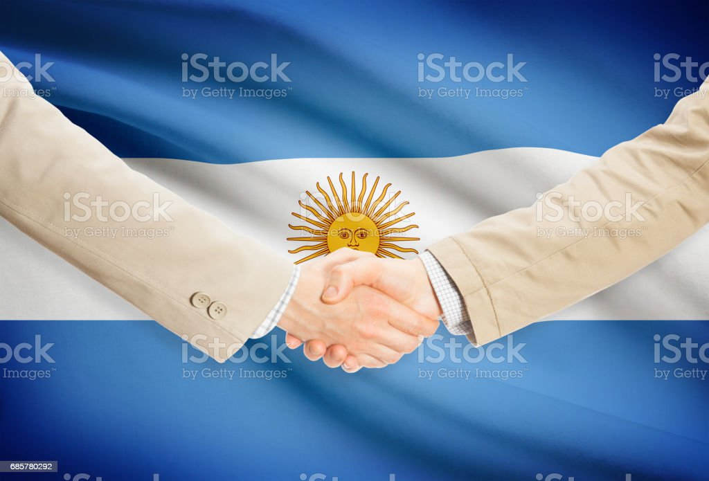 Businessmen handshake with flag on background - Argentina royalty-free stock photo