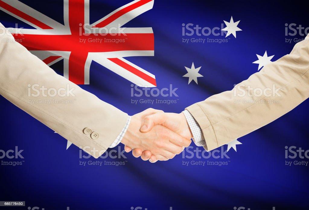 Businessmen handshake with flag on background - Australia royalty-free stock photo