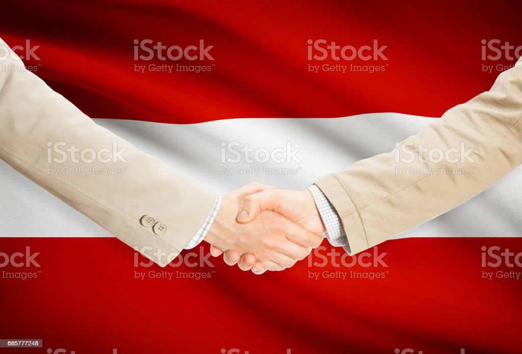 Businessmen handshake with flag on background - Austria royalty-free stock photo