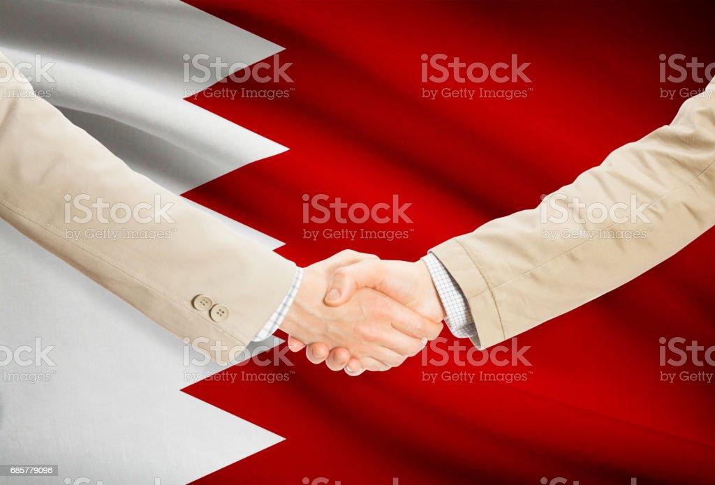 Businessmen handshake with flag on background - Bahrain royalty-free stock photo