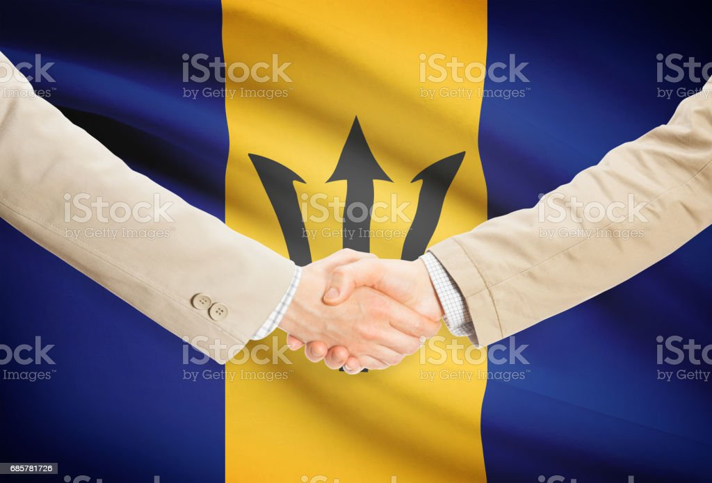 Businessmen handshake with flag on background - Barbados royalty-free stock photo