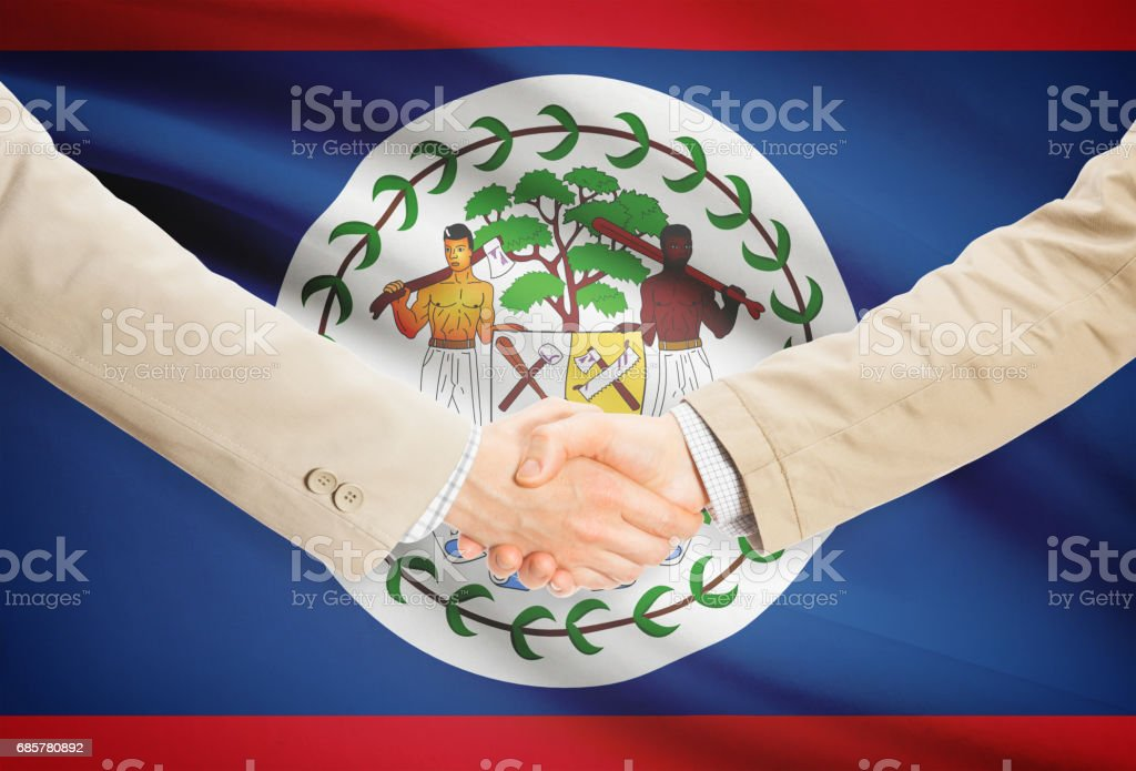 Businessmen handshake with flag on background - Belize royalty-free stock photo